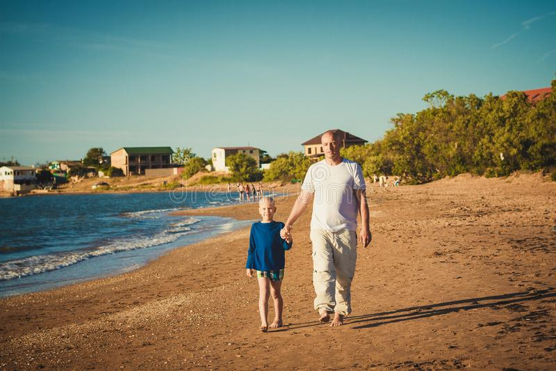 Happy father and son walking on the beach stock images