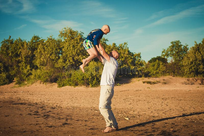 Happy father and son walking on the beach stock photo