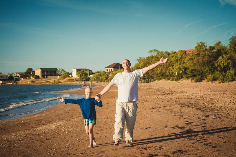 Happy father and son walking on the beach royalty free stock image