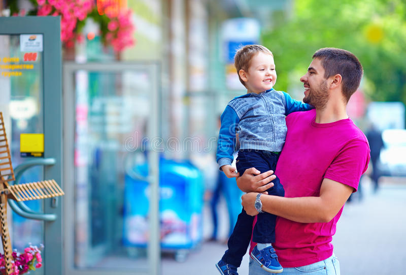 Happy father and son walking city street stock image