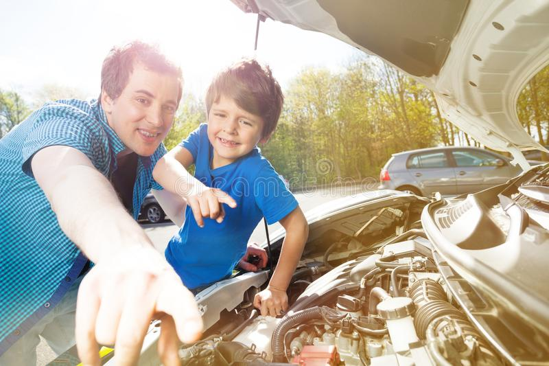 Happy father and son working on mechanism of a car stock images