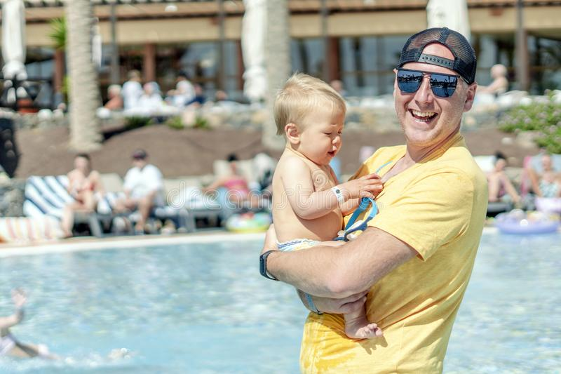 Happy father spending time with his baby son by the pool in the resort stock image