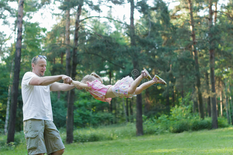 Happy father spinning around his daughter in green summer park outdoors. Happy father is spinning around his daughter in green summer park outdoors stock images