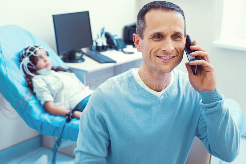 Happy father talking with wife about promising scan results stock photography