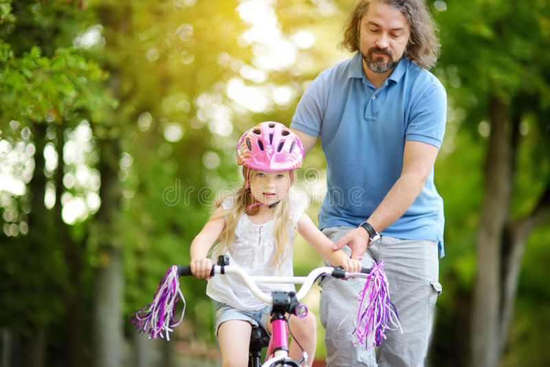 Happy father teaching his little daughter to ride a bicycle. Child learning to ride a bike. stock photography