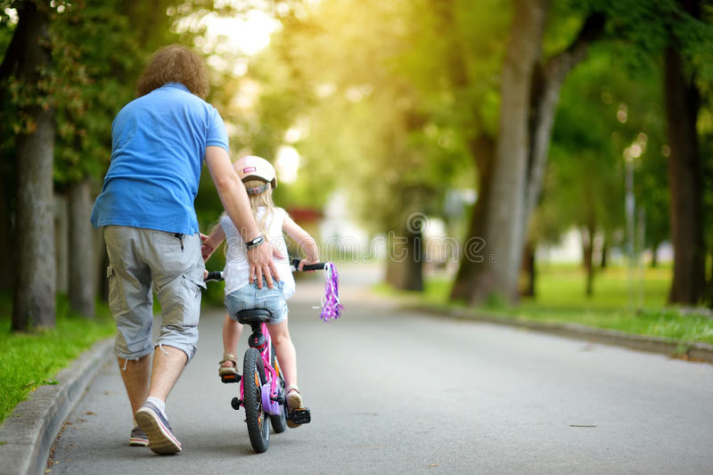 Happy father teaching his little daughter to ride a bicycle. Child learning to ride a bike. royalty free stock photos