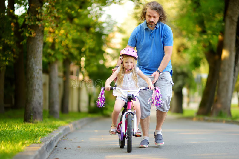 Happy father teaching his little daughter to ride a bicycle. Child learning to ride a bike. royalty free stock image