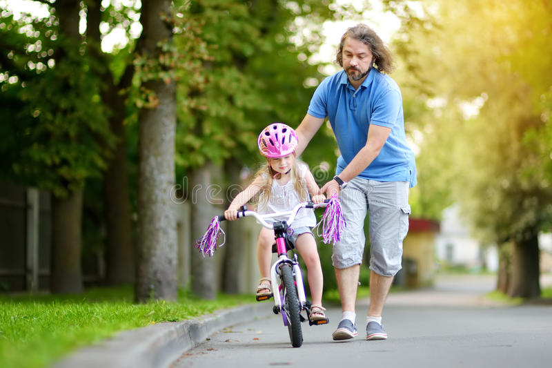 Happy father teaching his little daughter to ride a bicycle. Child learning to ride a bike. royalty free stock images