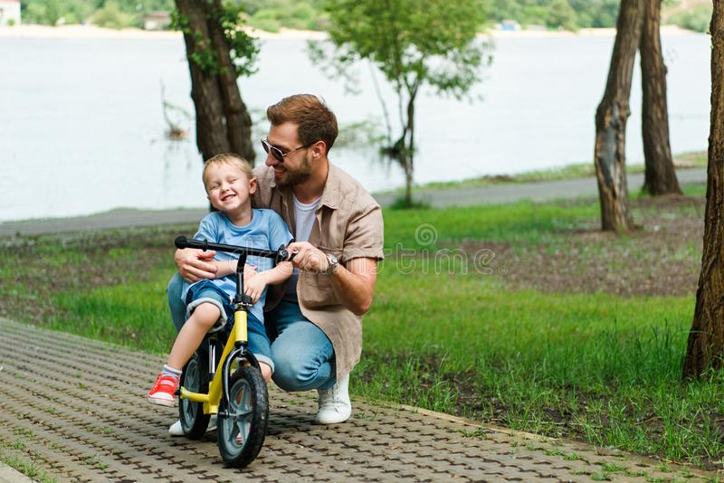 Happy father teaching son riding bike. At park royalty free stock photography