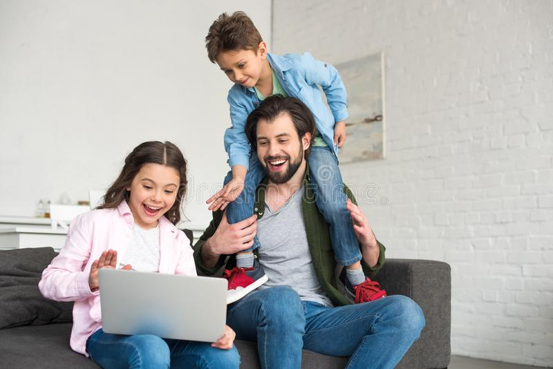 happy father with two cute kids sitting on sofa and using laptop stock photos