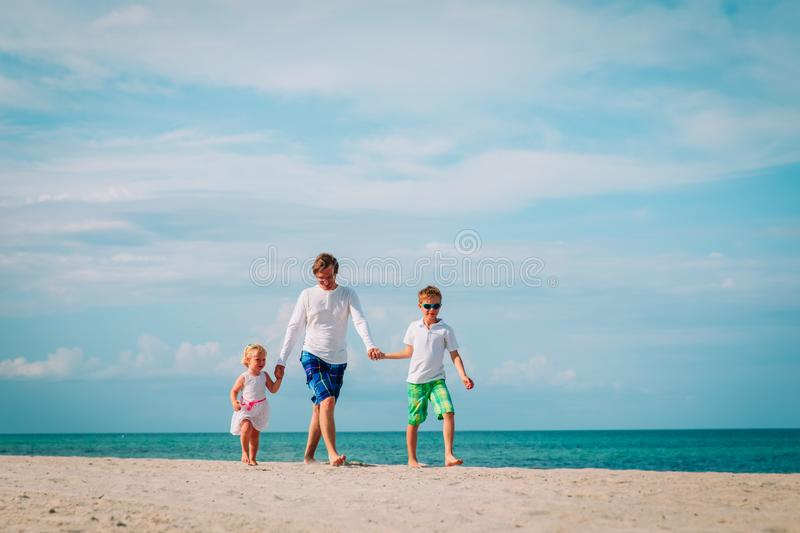 Happy father and two kids walking on beach stock photos