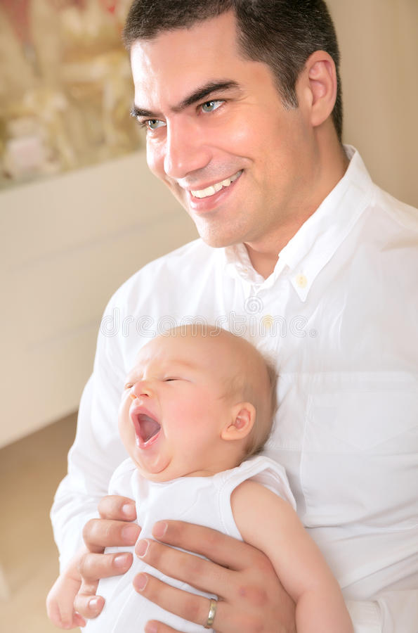 Happy father with yawning daughter on hands stock photography