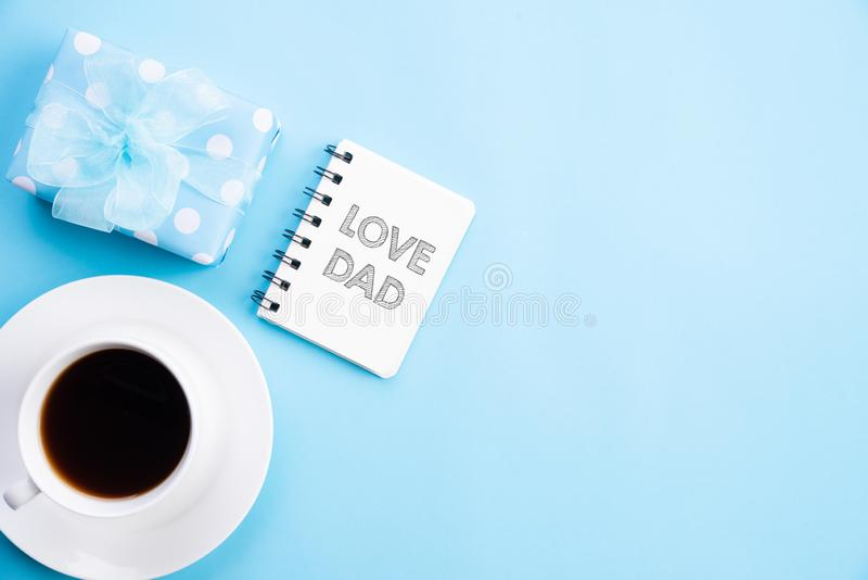 Happy fathers day concept. Top view of beautiful gift box, coffee mug with LOVE DAD text on bright blue pastel background.  stock photography