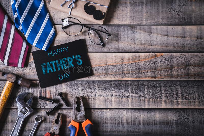 Happy fathers day concept. Top view of black paper tag with Happy father`s day text and left border of tools and ties, retro f. Glasses on dark wooden table stock images
