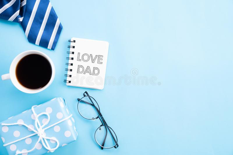 Happy fathers day concept. Top view of blue tie, beautiful gift box, coffee mug, glasses with LOVE DAD text on bright blue pastel. Background stock photography