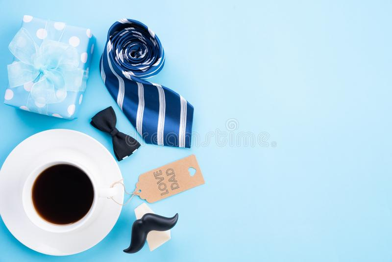Happy fathers day concept. Top view of blue tie, beautiful gift box, coffee mug, paper tag with LOVE DAD text on bright blue. Pastel background stock image