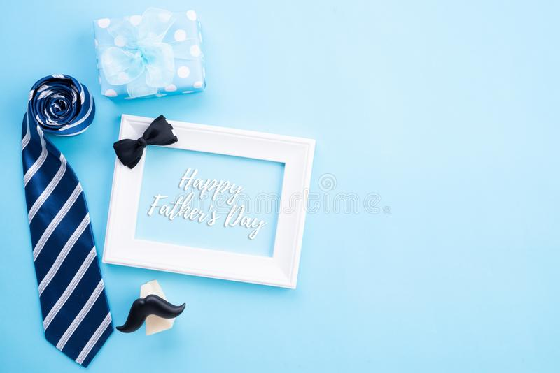 Happy fathers day concept. Top view of blue tie, beautiful gift box, coffee mug, white picture frame with happy father`s day text. On bright blue pastel stock photo