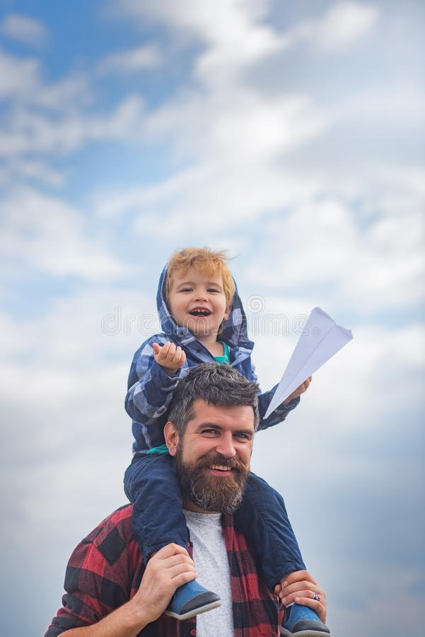 Happy fathers day. Dad and son are playing on sky background. Child sits on the shoulders of his father. Freedom to. Dream - Joyful Boy Playing With Paper stock photo