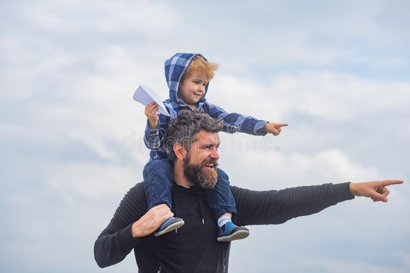 Happy fathers day. Dad and son are playing on sky background. Father and son building together a paper airplane. Portrait of happy father giving son piggyback stock image