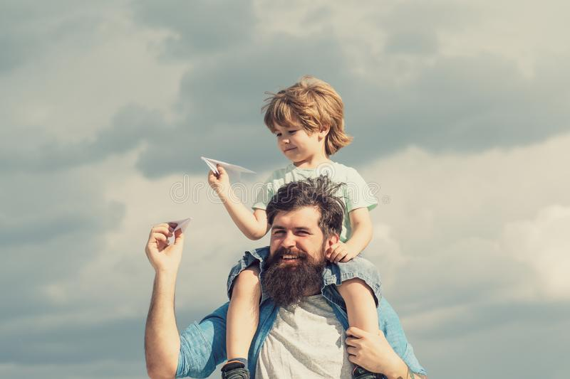 Happy fathers day. Dad and son are playing on sky background. Father and son in the park. Freedom to Dream - Joyful Boy. Playing With Paper Airplane royalty free stock photos
