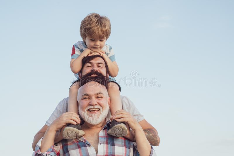 Happy fathers day. Father and son enjoying outdoor. Men generation: grandfather father and grandson are hugging looking. At camera and smiling stock image