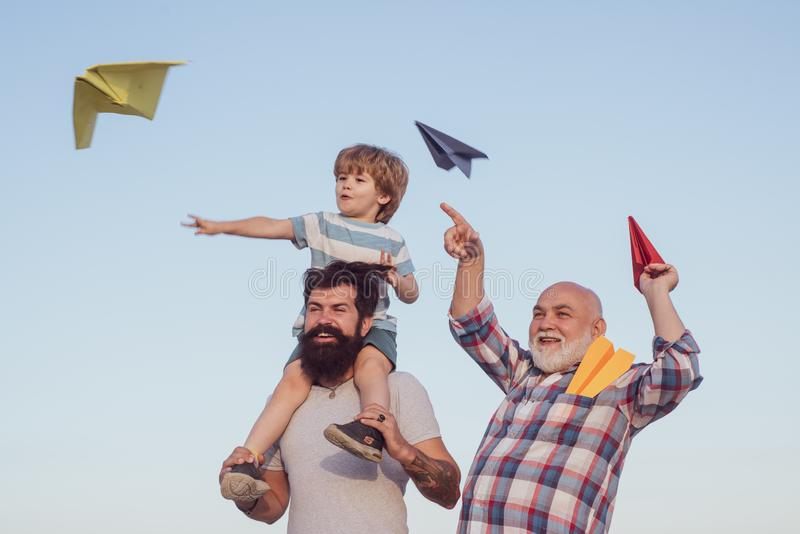 Happy fathers day. Happy grandfather father and grandson with toy paper airplane over blue sky and clouds background. Dream of flying. Generation of people and royalty free stock photo