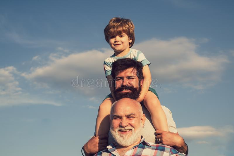 Happy fathers day. Grandfather playtime. Young boy with father and grandfather enjoying together in park on blue sky royalty free stock photos