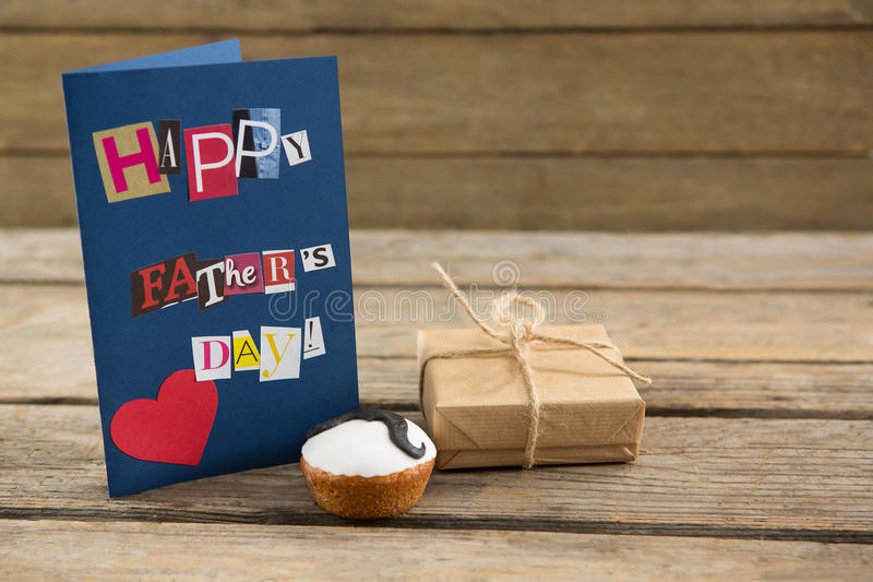 Happy fathers day greeting card with gift box on table stock image