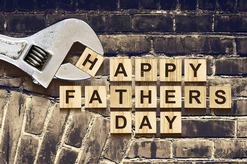 Happy Fathers Day inscription on wooden cubes with working tools on an old vintage brick wall. Happy Father`s Day Concept. Greeti stock images