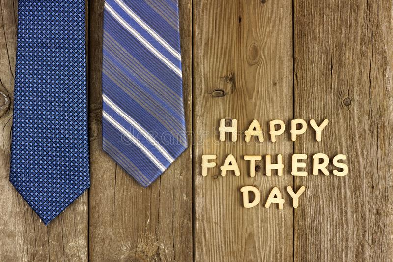 Happy Fathers Day letters with ties on rustic wood stock image