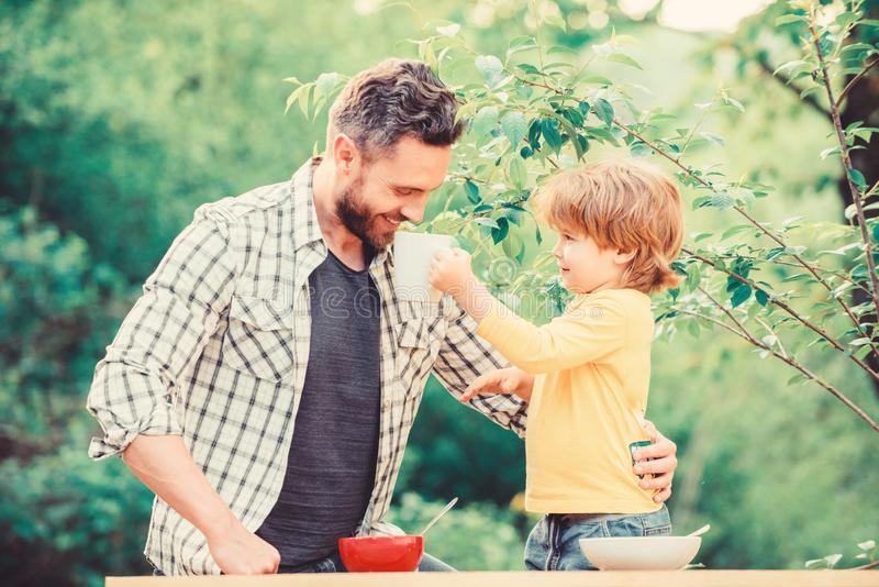 Happy fathers day. Little boy with dad have breakfast. son and father eating milk porridge. childhood happiness. Baby stock photo