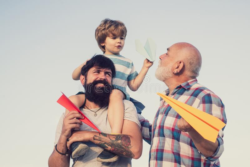 Happy fathers day. Young boy with father and grandfather enjoying together in park on blue sky background. Generations. Men. Family holiday and togetherness stock photos