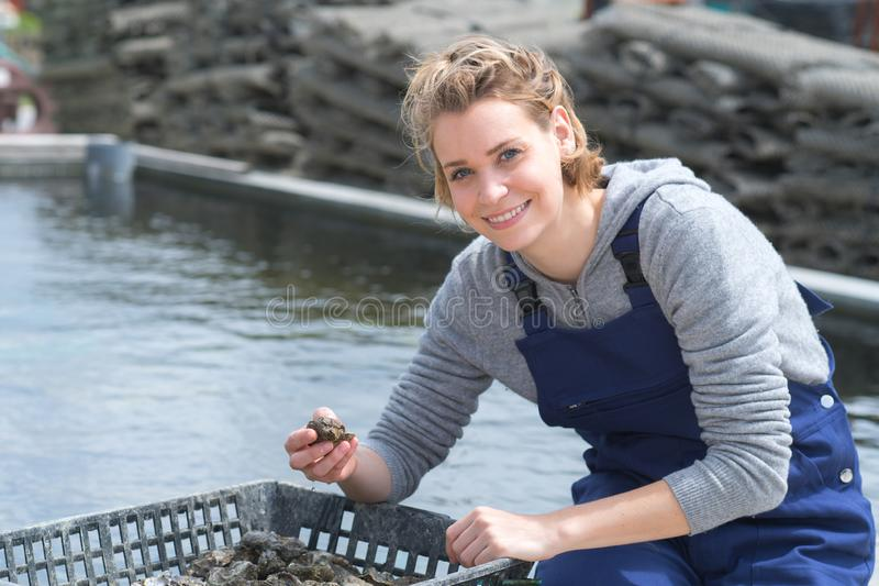 Happy femake worker at fish and mussel farm. Fish royalty free stock photos