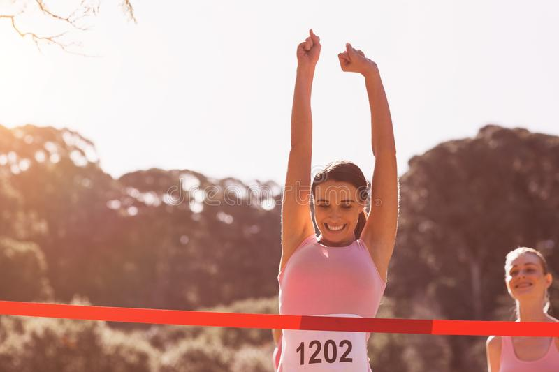 Happy female athlete with arms raised crossing finish line stock photo