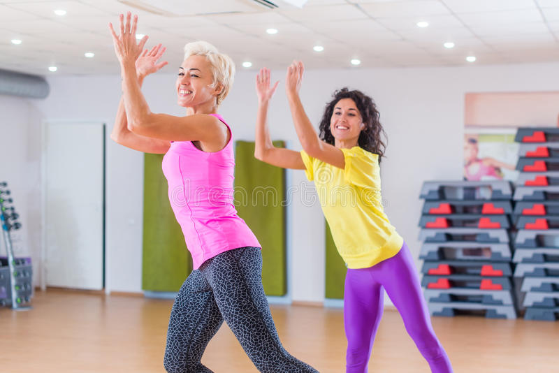 Happy female athletes doing aerobics exercises or Zumba dance workout to lose weight during group classes in fitness. Center royalty free stock photos