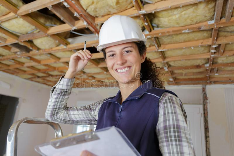 Happy female builder with clipboard stock photography
