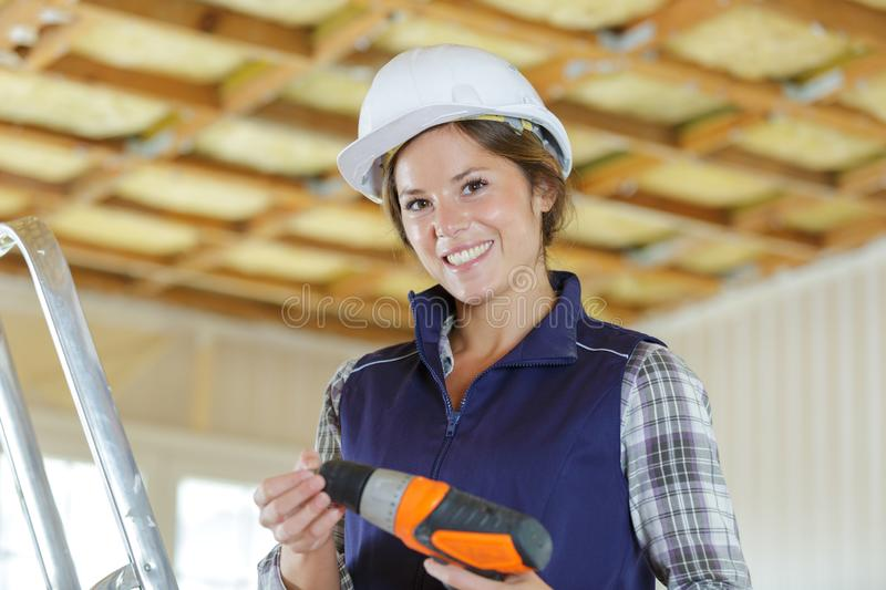 Happy female builder holding drill royalty free stock photo