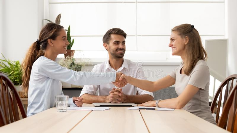 Happy female business partners handshake sign contracts with lawyer mediation stock image