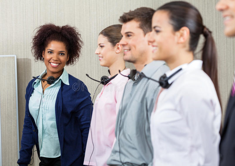 Happy Female Call Center Employee Standing With. Portrait of happy female call center employee standing with team at call center stock photo