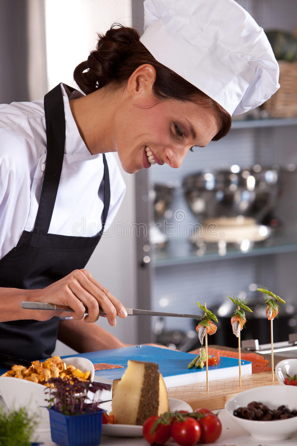 Happy female chef. Attractive and happy female chef preparing an amuse royalty free stock photography