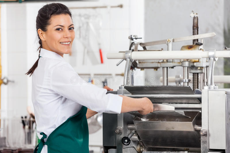 Happy Female Chef Processing Ravioli Pasta In. Portrait of happy female chef processing ravioli pasta in machine at commercial kitchen stock photo