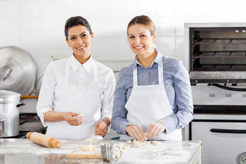 Happy Female Chefs Preparing Pasta At Counter royalty free stock image