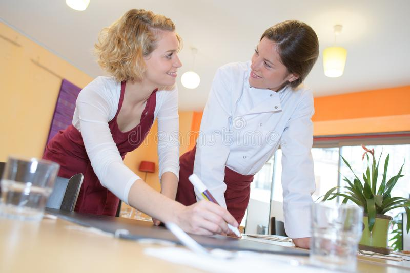 Happy female chefs working together stock images
