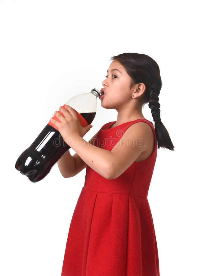 Happy female child holding big soda bottle drinking in sugar drink abuse stock images