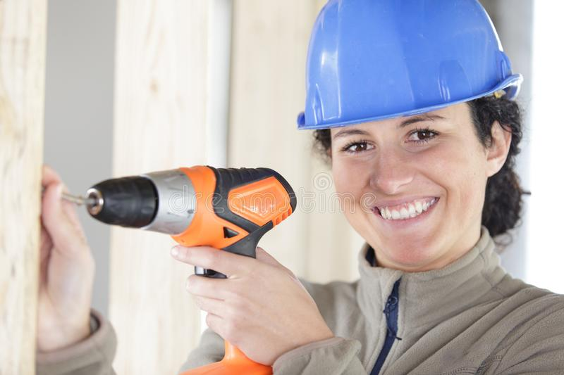 Happy  female construction worker in hard-hat drilling concrete wall stock photos