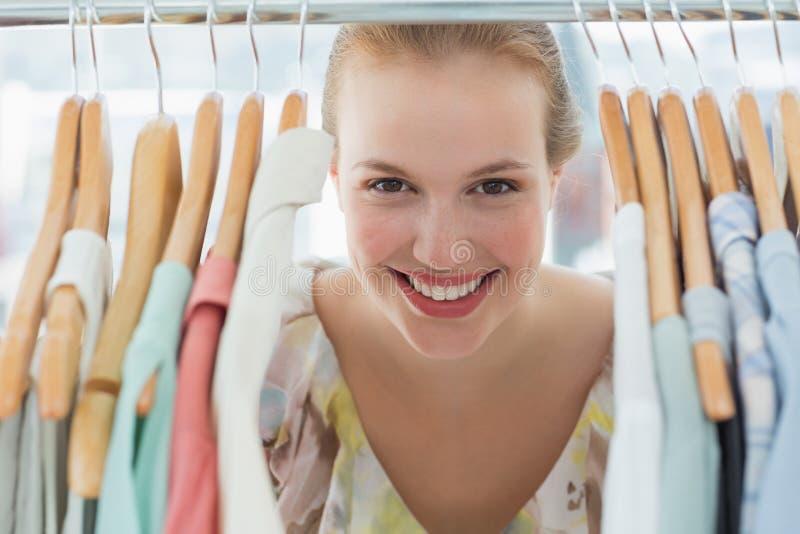 Happy female customer amid clothes rack stock photos