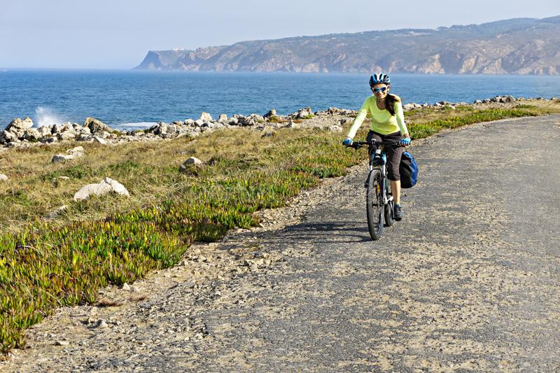 Happy female cyclist rides bicycle on road along ocean shore. royalty free stock photo