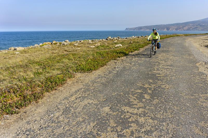 Happy female cyclist rides bicycle on road along ocean shore. stock photos