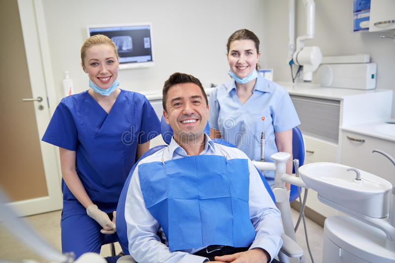 Happy female dentists with man patient at clinic. People, medicine, stomatology and health care concept - happy female dentists with men patient at dental clinic royalty free stock image