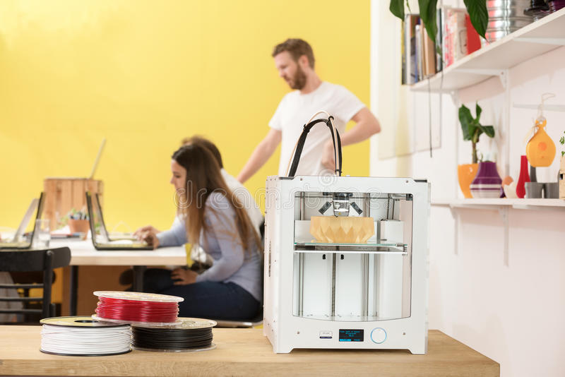 Happy Female Designer Using Laptop By 3D Printer In Studio stock photography